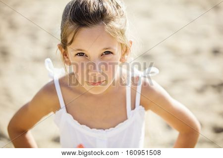 Young girl looking suspiciously while standing on beach