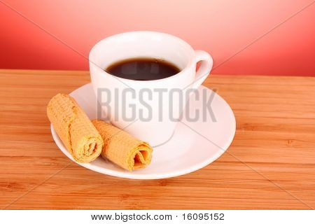 Cup of coffee with two  sweet  rolls on the table