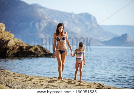 Young woman and her daughter walking along sandy beach