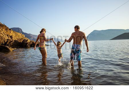 Caucasian family with little son having fun on beach