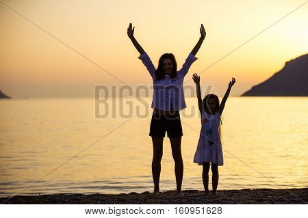 Mother and daughter lifting arms while standing on the beach at sunset