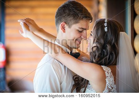 Happy young bride and groom going to kiss indoors