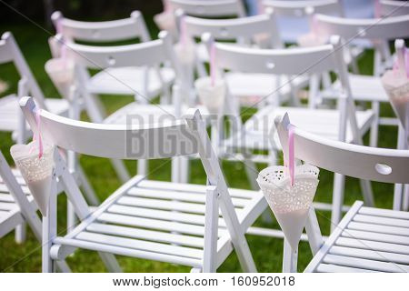 White chairs on the green grass for wedding ceremony