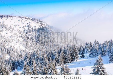 Panorama of ski resort, ski slope, people skiing, mountains covered with snow