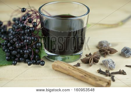 Fresh glass of elderberry juice with spices and a bunch of fresh berries for a healthy nutritional drink