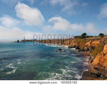 Pigeon Point Lighthouse on California coast. Ocean waves splashing yellow stone cliffs