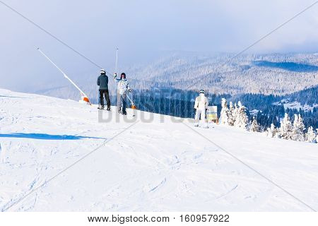 Kopaonik, Serbia - January 22, 2016: Ski resort and ski slope, people skiing down the hill, mountains view, fog