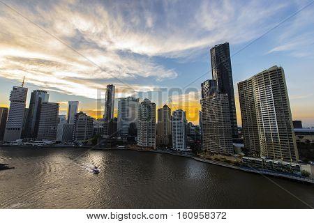BRISBANE, AUSTRALIA - December 5 2016: Brisbane City riverside and a river ferry under a colourful sunset
