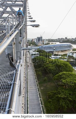 A climber climbing to the top of Brisbane Story Bridge, and pedestrian path below.