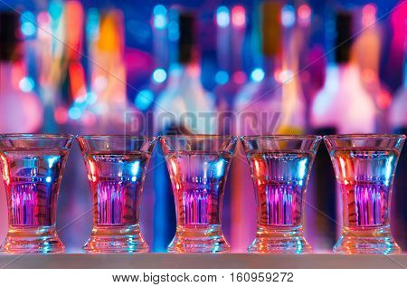 Five burning drinks in shot glasses on a bar counter standing in a row
