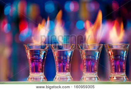 Four hot shot glasses standing in a row on a bar counter