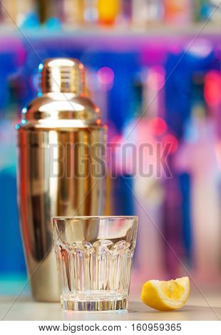 Picture of empty glass standing on a bar counter with lemon segment and shaker on background