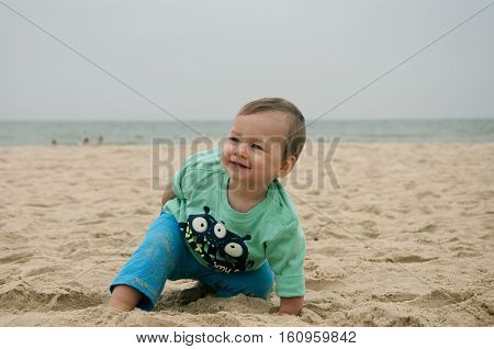 cheerfull baby playing in sand on vacations, summer trip.