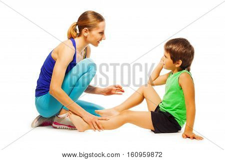 Young female instructor explaining how to do physical exercises to little sportsman, isolated on white