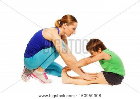Female trainer teaching kid boy working stretching leg muscles of back to warm up before training, isolated on white