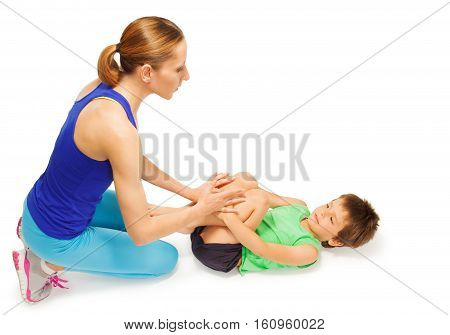 Five years old boy doing physical exercises, laying on the floor with his mom