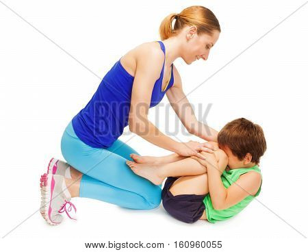 Sporty mother teaching her kid son making gymnastics, isolated on white