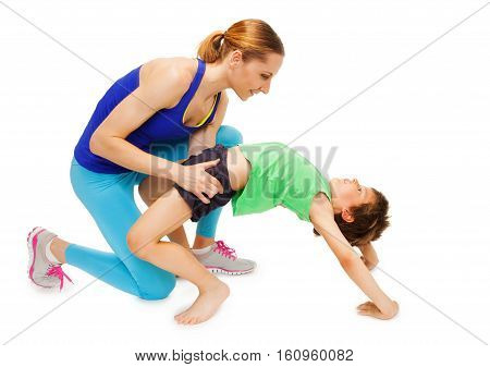 Mother helping her kid son making a crab posture, isolated on white