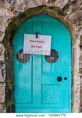 Wet paint sign on a freshly painted door at Portmeirion Gwyedd Wales.