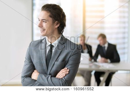 Portrait of young smiling businessman launched first effective business, setting himself up for successful career, independent and prosperous. Business hopes and dreams. Boss and business team concept
