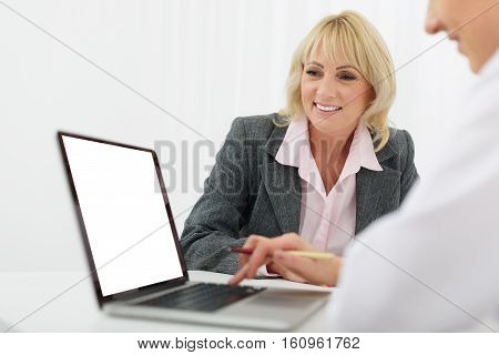 Confident general practitioner is using laptop at her office. Senior patient is looking at screen with interest. She is smiling