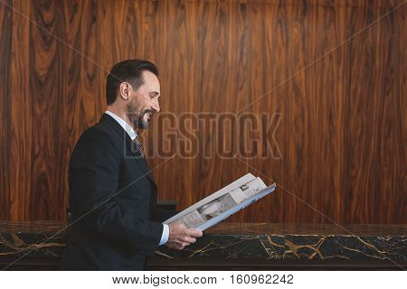 Informed of all developments. Smiling mature businessman reading newspaper in hotel lobby