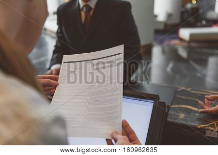 Standard checking procedure. Close up of female receptionist holding form to fill in while standing at reception