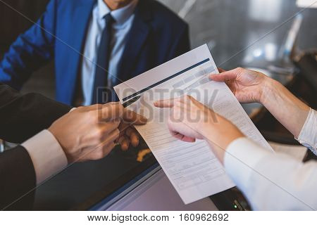Just signing in. Hotel receptionist showing for guests where to put his signature on letterhead