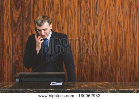 We always looking forward to your arrival. Adult clerk standing at reception desk and making reserve while holding telephone in hand