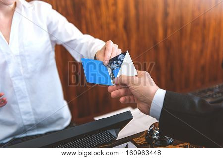 This is your pass. Close up of female receptionist giving cardkey to male customer at reception in hotel
