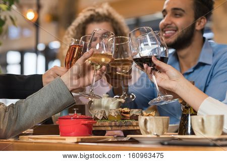 Young Business People Group Drink Wine Sitting Restaurant Table, Friends Hold Glasses Toasting Smiling Mix Race Men Women