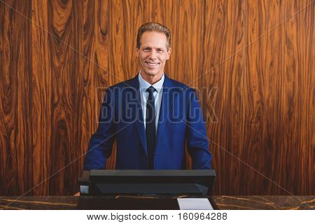 Confident and successful leader. Smiling mature hotelier looking content while standing reception desk in lobby