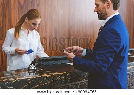 Instantly connected to his clients. Smiling businessman checking his mobile phone at reception in hotel. Female receptionist registering customer and holding cardkey in her hand