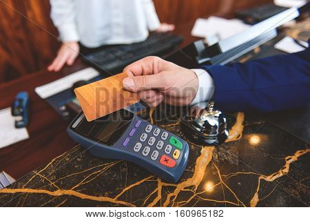No cash, only plastic. Close up of man hand holding credit card during registration at reception