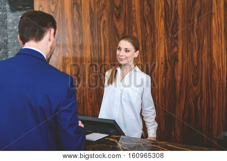 I hope you enjoy your stay. Friendly female receptionist looking at customer and smiling while standing behind reception desk