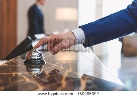 Checking in at reception. Close up of hand of man using bell with hotel employee standing on background