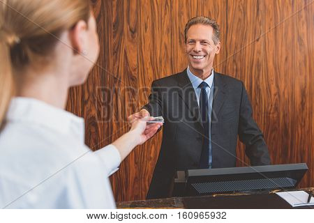 Check-in process. Friendly mature male receptionist passing over card key to female guest at reception desk