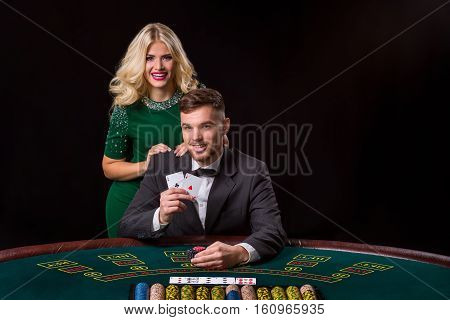 couple playing poker at the green table. The blonde girl and a guy in a suit. happy win, two