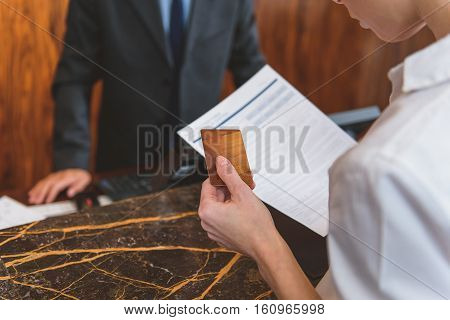 I take this apartment. Close up of female hand holding credit card and application form while standing in reception area
