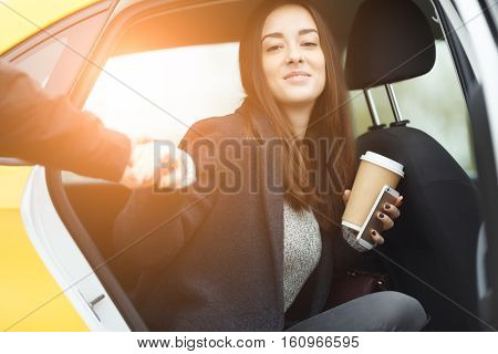 Guy takes hand brunette sitting in yellow taxi