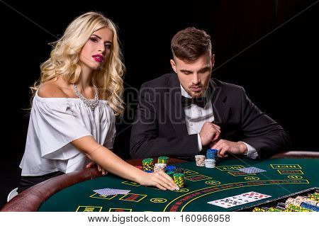 couple playing poker at the green table. The blonde girl and a guy in a suit. chips bets