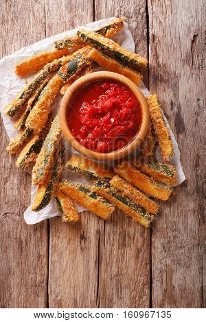 Fried Slices Of Zucchini With Parmesan Cheese And Breading And Tomato Sauce Closeup On A Table. Vert