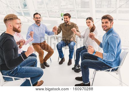 Hilarious group is sitting in light room. They taking hand of each other