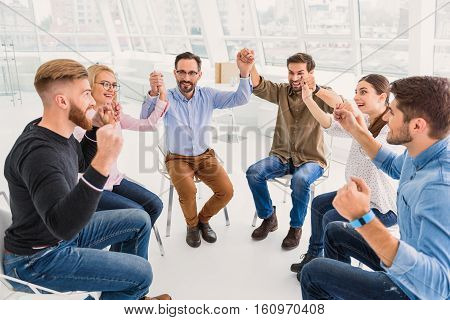 Happy group is sitting and holding hands. They also raising them up with funny smiles