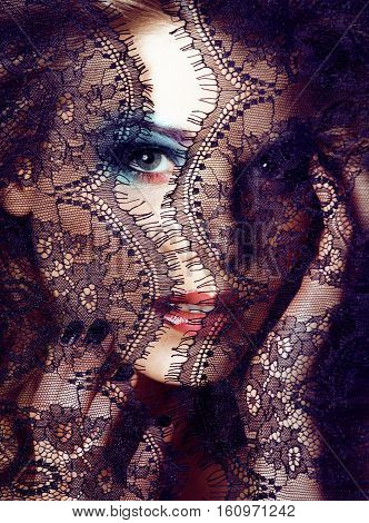 Portrait of beauty blond young woman through black lace close up mistery