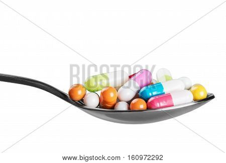 different colored pill on a spoon isolated on white background white background.