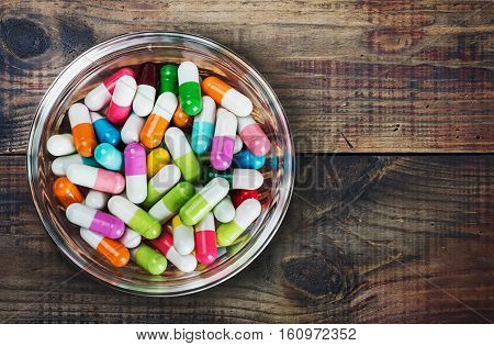 different colored pills on a wooden table