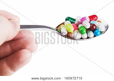 different colored pill on a spoon in his hand isolated on white background