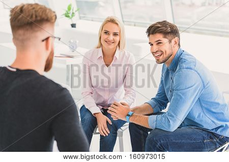 Smiling people are sitting in room together and talking. They in good mood
