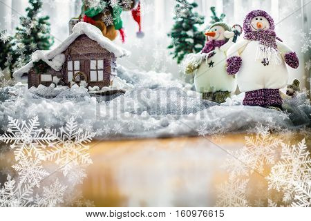 Merry Christmas Card with Happy Snowman near their Home wearing Winter Scarfs and Hats with snowflakes space for text... Shot using very Shallow Depth of field.